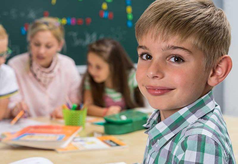 Grundschüler mit lernenden Kindern im Hintergrund