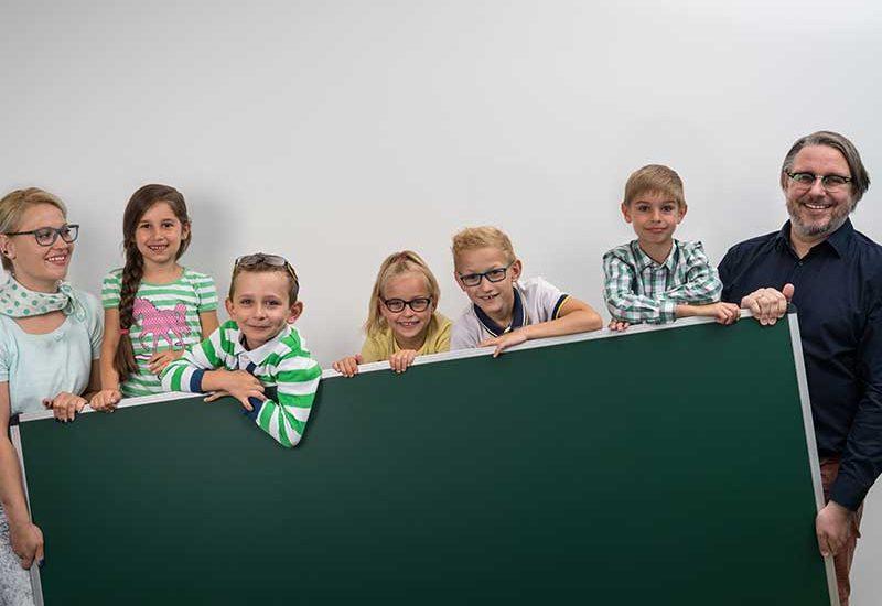 Schüler und Nachhilfelleiter hinter der Tafel