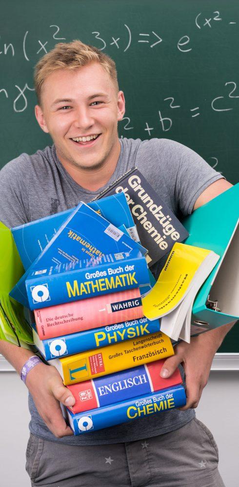 Schüler mit Bücherstapel in de Armen