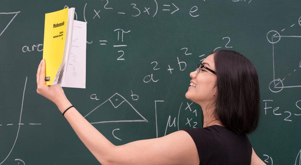 Schülerin rechnet Matheaufgaben an Tafel